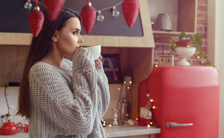 Attractive brunette girl drinking coffee at decorated kitchen for Christmas holiday