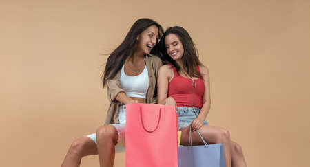 Happy Two friends holding shopping bags