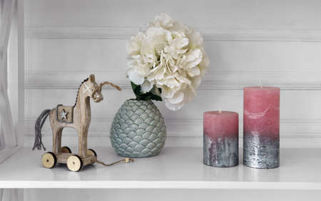 Home accessories vase wooden horse and candles on white wooden shelf