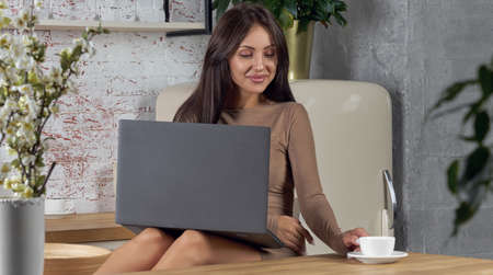 Cheerful girl working on laptop at the kitchen and drinking coffee Banque d'images