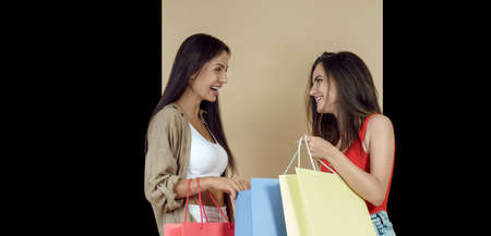 Two young women carryig shopping bags on black and beige background Stock fotó