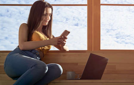 Girl using smartphone and laptop while sitting on window sill