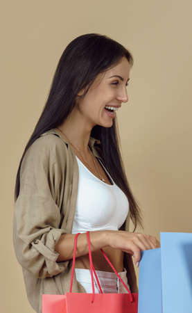 Portrait of young woman laughing and holding shopping bags Stock fotó