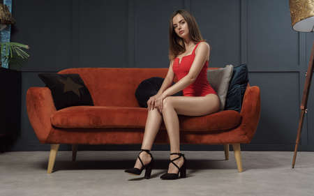 Portrait of attractive woman wearing red body and sitting on modern sofa