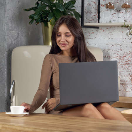 Young woman using laptop at the kitchen while drinking coffee