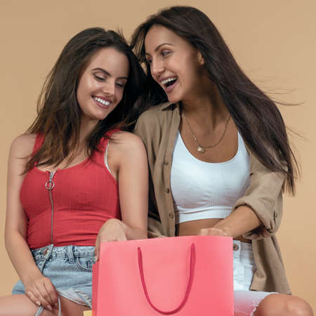 Two young women holding a shopping bag and laughing Stock fotó