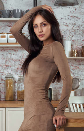 Young sexy woman in tight dress standing at the kitchen