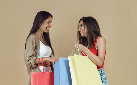 Two cheerful friends holding shopping bags on beige background