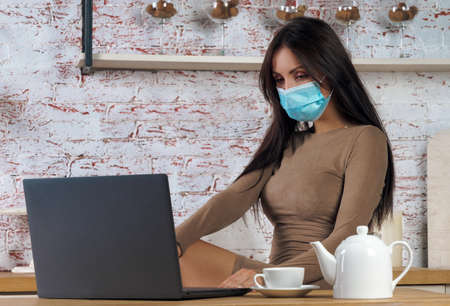 Woman wearing protective mask while working online