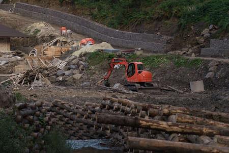 Excavator digging on construction site beside river