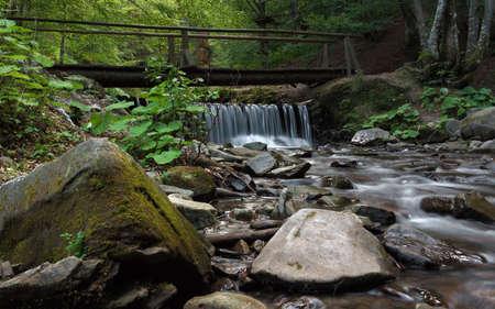Flowing waterfall under wooden bridge