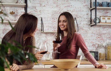 Two young women enjoying their time and drinking glass of wine at the kitchen Stock fotó