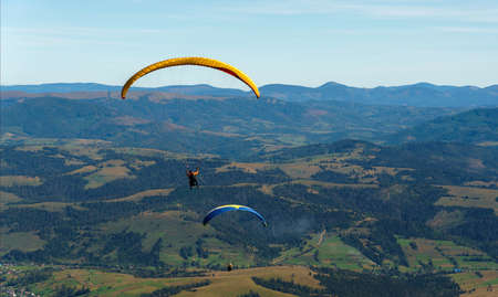 Two paragliders flying above mountains