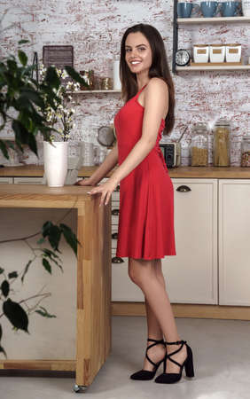 A young woman in red dress standing at the kitchen