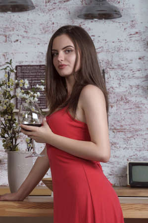 Young woman in red dress standing at the kitchen and drinking a glass of wine
