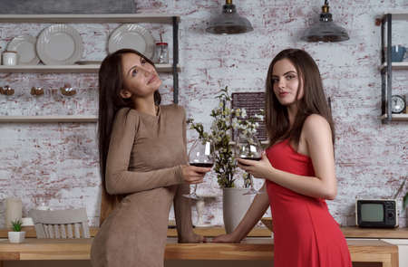 Two women friends drinking wine at the kitchen together