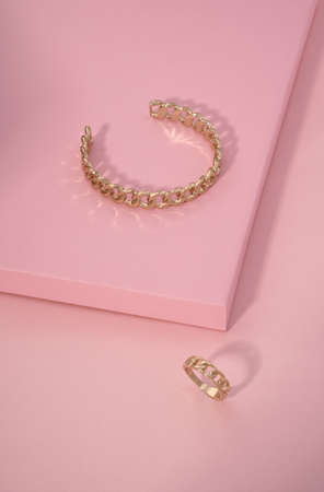 Chain shape golden bracelet and ring on pink color background with copy space Stock fotó