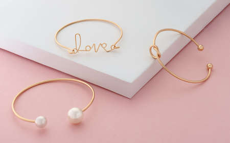 Three modern golden bracelets on white and pink colors background Stock fotó