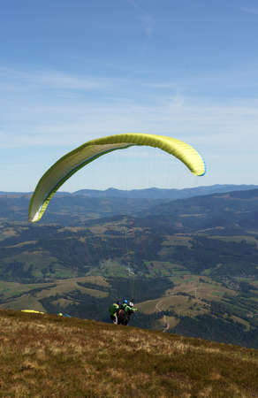 Paraglider preparing to jump from mountain clif