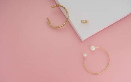 Top view of golden jewelries on pink and white background Stock fotó