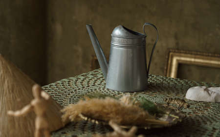 Vintage metal jug and on green table with copy space. Painting style Zinc pitcher on covered table Stock fotó