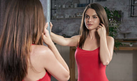 Young woman in red dress and looking at her self in the mirror