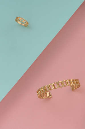 Chain shape golden bracelet and ring on slanted paper background
