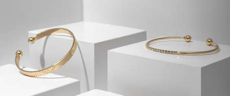 Two Golden bracelets on white geometric background