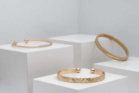 Three golden modern bracelets on white boxes