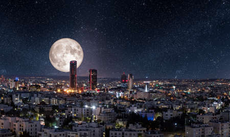 Full moon behind modern buildings in the new downtown of Amman city