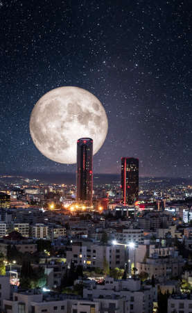 Full moon above modern buildings in the new downtown of Amman city