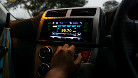 The close up view of the smart multimedia touchscreen radio panel in the car with street light flare during the rain and hand holding gear stick. Car system control screen interface modern design. 写真素材