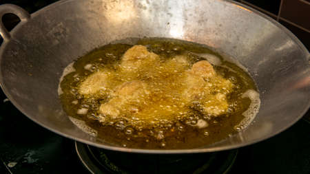 Close up view of the frying chicken in a hot boiling oil in the metal wok.