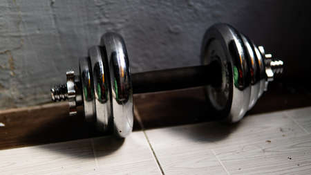 Metal dumbbell equipment with wall background rolling on the floor. Use for fitness and healthy training purposes. Suitable to use for wallpaper.