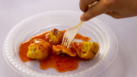 Cucur Udang or Prawn Fritters covered with chilli sauce on isolated white background,it's a common tea time cake among Malaysians.A popular snack in South East Asian countries.