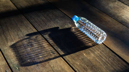 Sunlight rays from outside reflected onto small plastic bottle on the wooden floor and formed a big bottle shadow. Inspirational and hidden opportunities concept. Small outer self, big inner self. Stock Photo