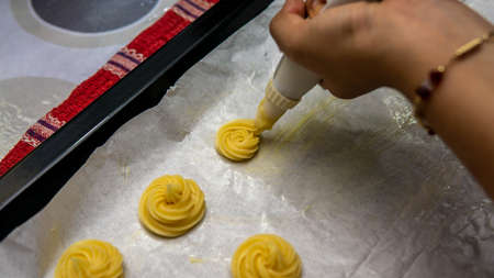Close up view of girl making cream puff pastry ball using the piping bag in a row before baking it into the oven. Imagens