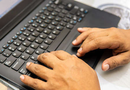 Close up of a man using computer doing work on a table. Working from home concept. Hand fingers clicking laptop keyboard. Standard-Bild