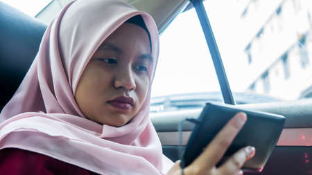 Portrait of Malay Asian muslim teenager girl using earphone listening to music or watch online video on her smartphone in the car.
