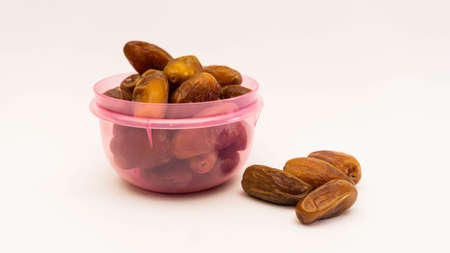 Phoenix dactylifera, commonly known as dates or kurma in purple plastic container on isolated white background. Stock Photo