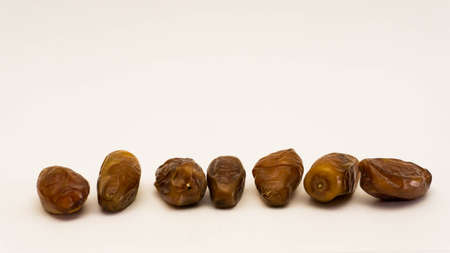 A row arrangement of phoenix dactylifera, commonly known as dates or kurma on isolated white background. Selective focus.
