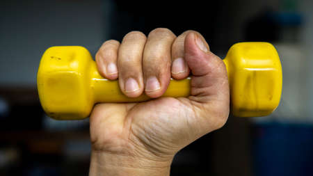 Close up view of woman hand holding a yellow 1 kilogram light weight mini dumbbell. Doing exercise at home. Healthy lifestyle concept. Keep fit.
