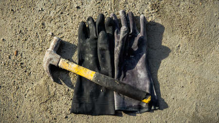 Flat lay of rusty metal hammer and construction white hand glove on grunge cement background with natural light and shadow. Labor day concept with empty copy space. 版權商用圖片