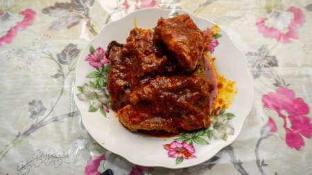 Close up view of homemade Ayam Masak Merah, a Malaysian traditional dish served in a plate. Chicken is cooked with red chili, tomatoes and sambal sauce. Stock Photo