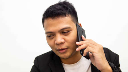A portrait of young Asian businessman having a serious talk and conversation on the phone with isolated white background. Career business job concept. Standard-Bild