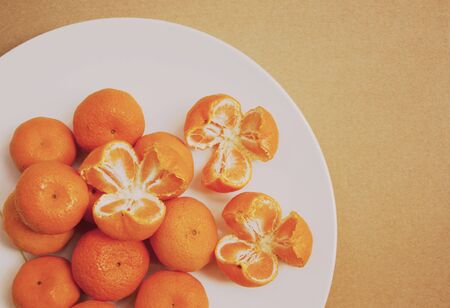 Three rip oranges and round oranges on white plate on brown background