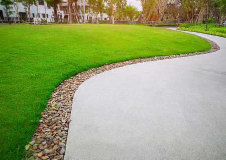 Smooth green grass lawn and gray curve pattern walkway, sand washed finishing on concrete paving with brown gravel border, trees with supporting and shrub in a good care maintenance landscape and garden