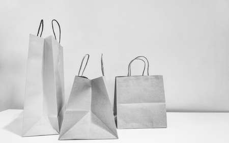 The gray empty paper shopping bags on the table and the light grey wallpaper, black and white photo