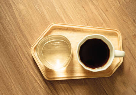 Top view photo, a white cup of americano black coffee and a glass of mineral water on wooden tray on brown wooden texture background under sunlight morning