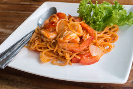 Close up stir fried spaghetti and prawn with tomato sauce